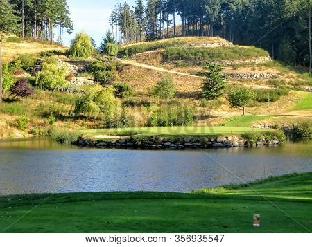 A View From The Tee Box Of A Beautiful Island Green Par 3 Surrounded By Water At A Golf Course Outsi