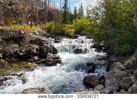 A Series Of Rocky Drops On A Fast Flowing River Create A Beautiful Waterfall In An Autumn Colored Fo