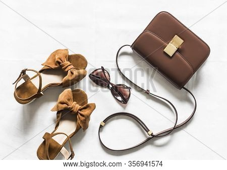 Cross Body Brown Leather Bag, Suede Wedge Sandals And Sunglasses On A Light Background, Top View. Fa