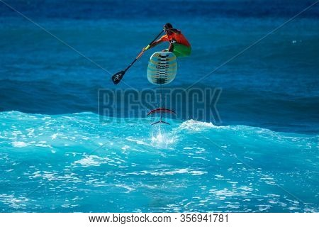OAHU, HI / USA - DECEMBER 01, 2018: Surfer jumps on a hydrofoil surfboard and shows the fins