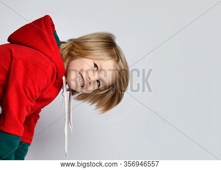 Portrait Of Happy Frolic Smiling Active Blond Kid Boy In Dark Gray And Red Hoodie Is Looking Out Fro