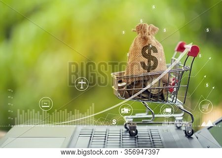 Shopping Cart - Trolley And Coins, Us Dollar Bags On Notebook Keyboard With Graph Growth Business In