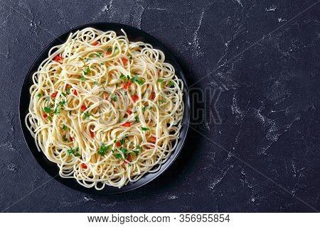 Pasta Aglio, Olio E Peperoncino, Italian Spaghetti With Garlic, Chili Pepper And Olive Oil On A Blac