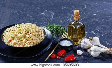 Pasta Aglio, Olio E Peperoncino, Italian Spaghetti With Garlic, Chili Pepper And Olive Oil In A Blac