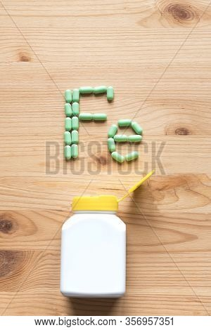Iron Supplement Pills, Anemia Treat. Green Pills Forming Shape To Fe Alphabet On Wooden Background,