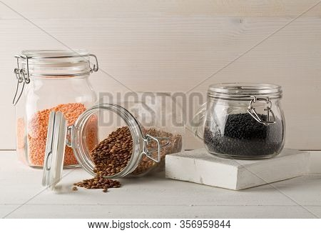 Different Assorted Lentils Mix With Red, Brown And Black Beluga Lentils In Glass Storage Jars On Whi