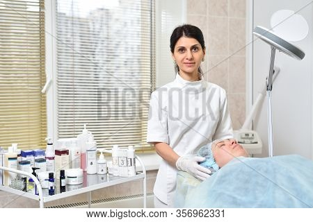 Stariy Oskol, Russia - December 26, 2019: Attractive Female Beautician Next To A Lying Client Before
