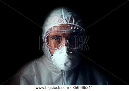 A Doctor With A Tired Look In A Respirator, Glasses And A Bacteriological Protection Suit. Low Key.