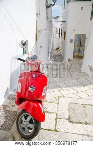 Ostuni, Italia - April 23, 2017: Red Vespa Scooter On Narrow Streets Of The Town Of Ostuni With Whit