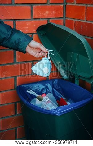 Male Hand Throws A Medical Mask Into A Trash Can