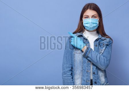 Close Up Portrait Of Woman Isolated Over Blue Background. Female Dresses Medical Flu Mask And Gloves