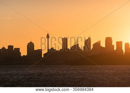 Sydney Cityscape With Bright Orange Sky And Dark Silhouettes Of Sydney Cbd Skyscrapers And Office An