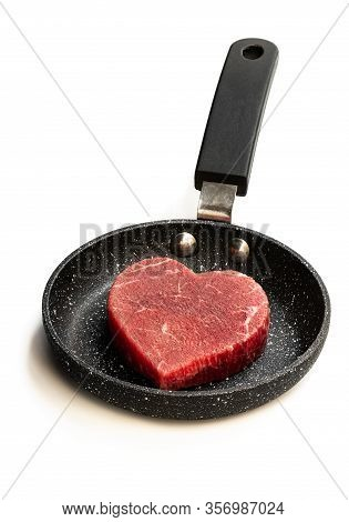 Heart  Shaped Raw Beef Meat On Small Frying Pan Isolated On White. Healthy Lifestyle Or Organic Food