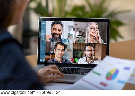 Back view of business woman talking to her colleagues about plan in video conference. Multiethnic business team using laptop for a online meeting in video call. Group of people smart working from home