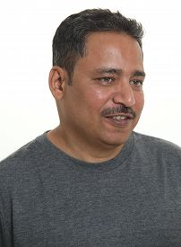An Indian Man In A Studio Against A White Background Looking Away