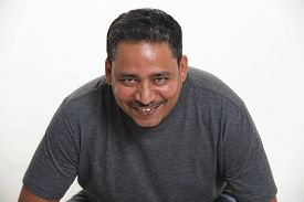 A Smiling Indian Man In A Studio Against A White Background Looking Up