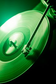 Green Vinyl Disc. Close-up. Techno Music. Black Background.
