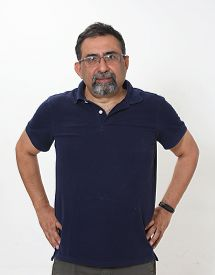 An Indian Man With A Goatee In A Studio Against A White Background. Wearing Spectacles And Looking T