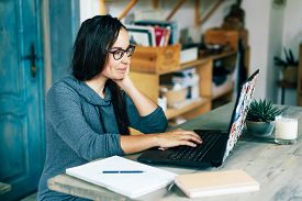 Ethnic Simpotic Dark-skinned Brunette Woman Working On A Laptop In The Interior Of A Cozy Living Roo