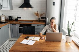 Work From Home. A Young Woman Uses A Laptop To Work In The Kitchen. She Looks At The Screen Intently