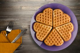 Belgian Waffles With Fork And Knife On A Black Wooden Background. Waffles On A Purple Plate Top View