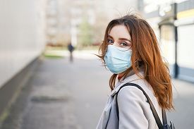 Young Woman With Beautiful Blue Eyes And Disheveled Hair Wearing Protection Face Mask Against Corona