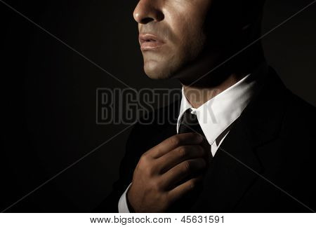 Young handsome man fixed tie isolated on black background, face part, successful businessman, mens fashion, glamour concept