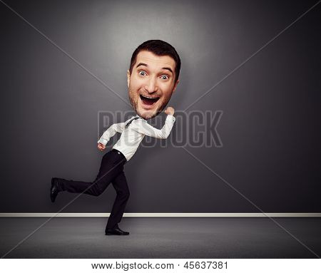 funny picture of merry running man with big head over dark background