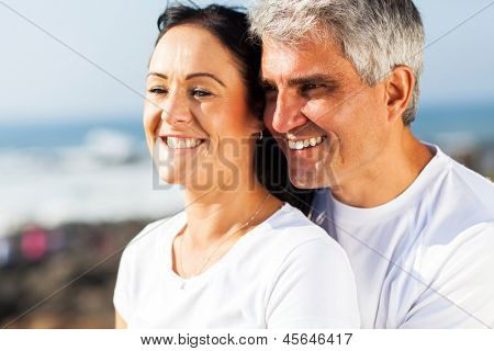 happy mid age husband and wife hugging at the beach