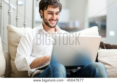 Young man relaxing on the sofa with a laptop poster