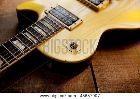Gold top guitar on rough wood surface.