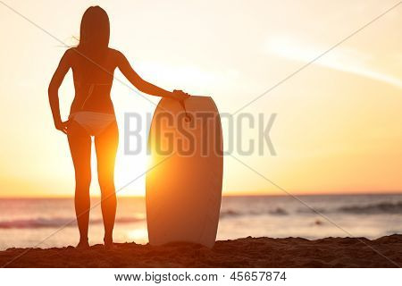 Water sport bodyboarding surfer woman on summer beach vacation holidays travel. Surfing girl holding bodyboard looking at ocean sea and sunshine. Beach bikini babe. Kaanapali beach, Maui, Hawaii.