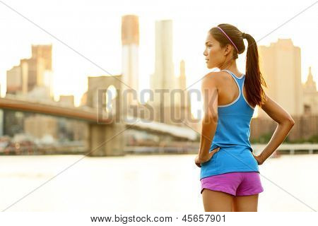 Fitness woman runner relaxing after city running and working out outdoors in New York City, USA. Girl looking and enjoying view of Brooklyn Bridge. Mixed race Asian Caucasian female model.