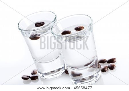 Two shot glasses of Sambuca with coffee beans, tilted view poster