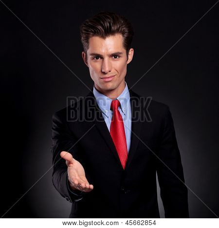 portrait of a young business man standing against a black background putting his hand out for a handshake while smiling to the camera