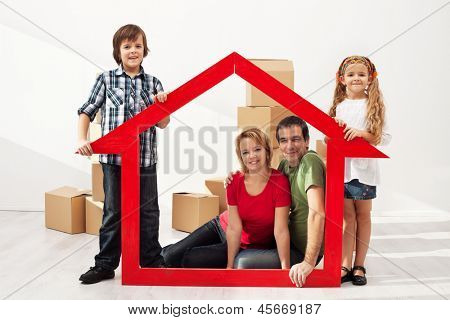 Happy family with two kids moving into their new home - sitting among cardboard boxes