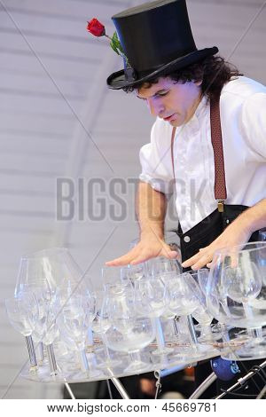 MOSCOW - AUGUST 10: Artist holds lot of glasses on stage at festival of street theater and carnival culture Once in park it garden named Bauman, on August 10, 2012 in Moscow, Russia.