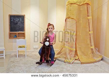 Portrait of little girl on hobbyhorse in playroom
