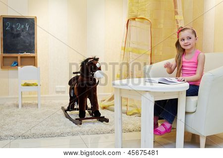 Little girl sits in big armchair and views book in playroom