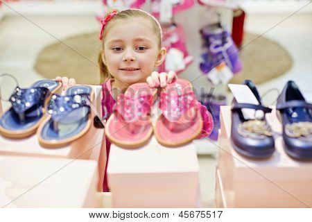 Little girl looks up on toeless shoes that stands on top of shoe boxes