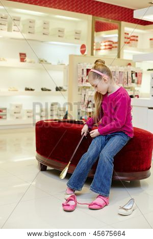 Little girl puts on shoe, helping herself by shoehorn in store poster