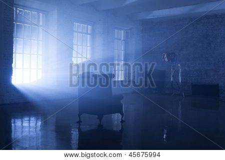 A seat in a blue backlight in studio with three windows, filmed in a rented public studio.