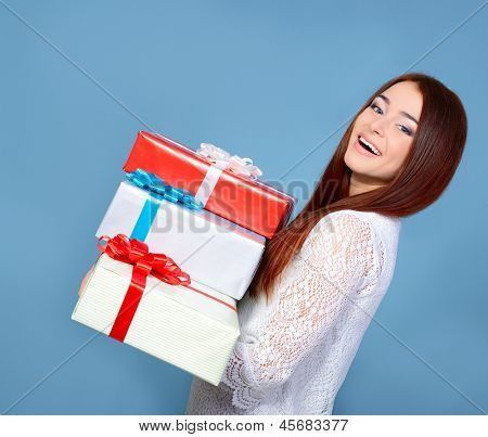 cheerful attractive girl with gift boxes over blue background