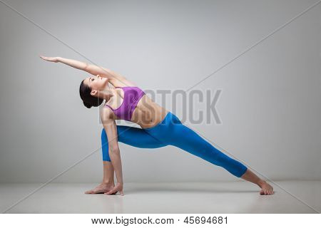 young beautiful yoga posing Utthita Parsvakonasana on a gray studio background