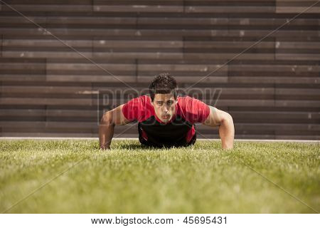 Athlete male at the city park making some push up poster