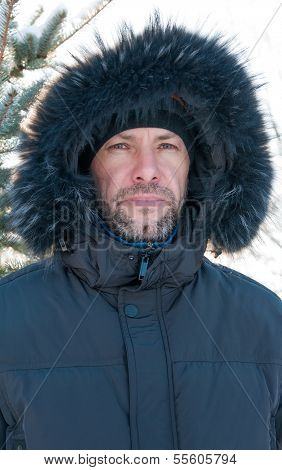 Portrait Of Confident Man Wearing Fur Hooded Parka Coat At The Spruce