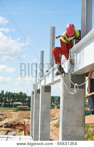 worker joiner in uniform and safety protective equipment at metal construction frames installation and assemblage