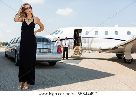 Full length of wealthy woman in elegant dress standing against limousine and private
