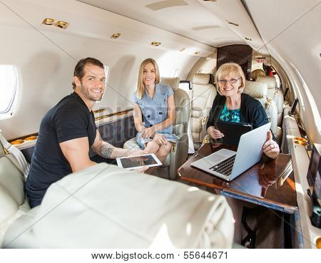 Portrait of business people having discussion over laptop on private jet