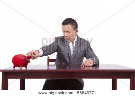 Young businessman pointing towards his piggy bank
